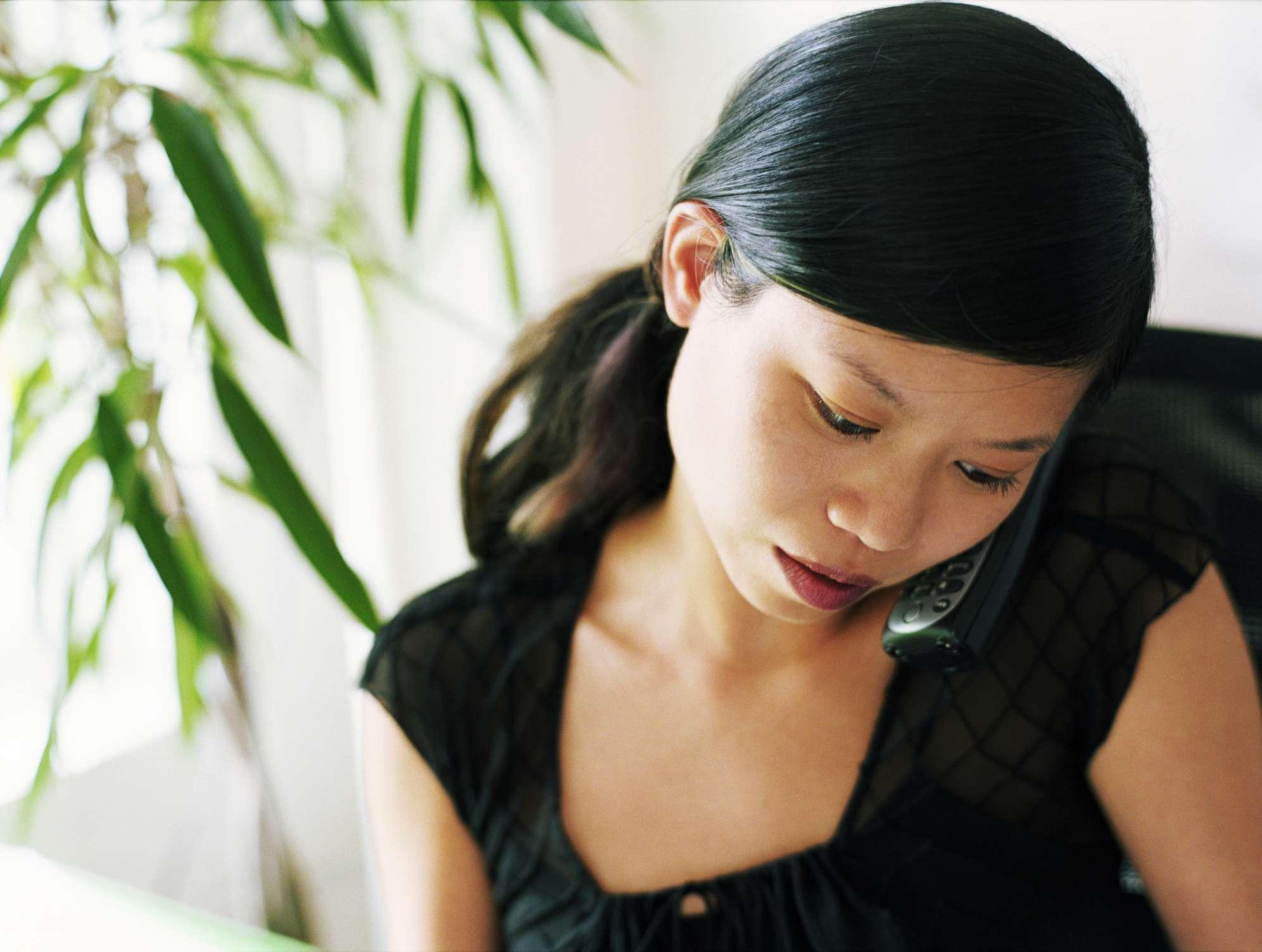 Woman Cradling the phone between head and shoulders
