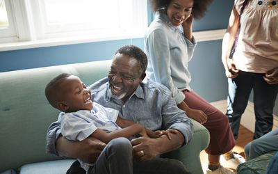 grandfather holding and laughing with grandson on couch