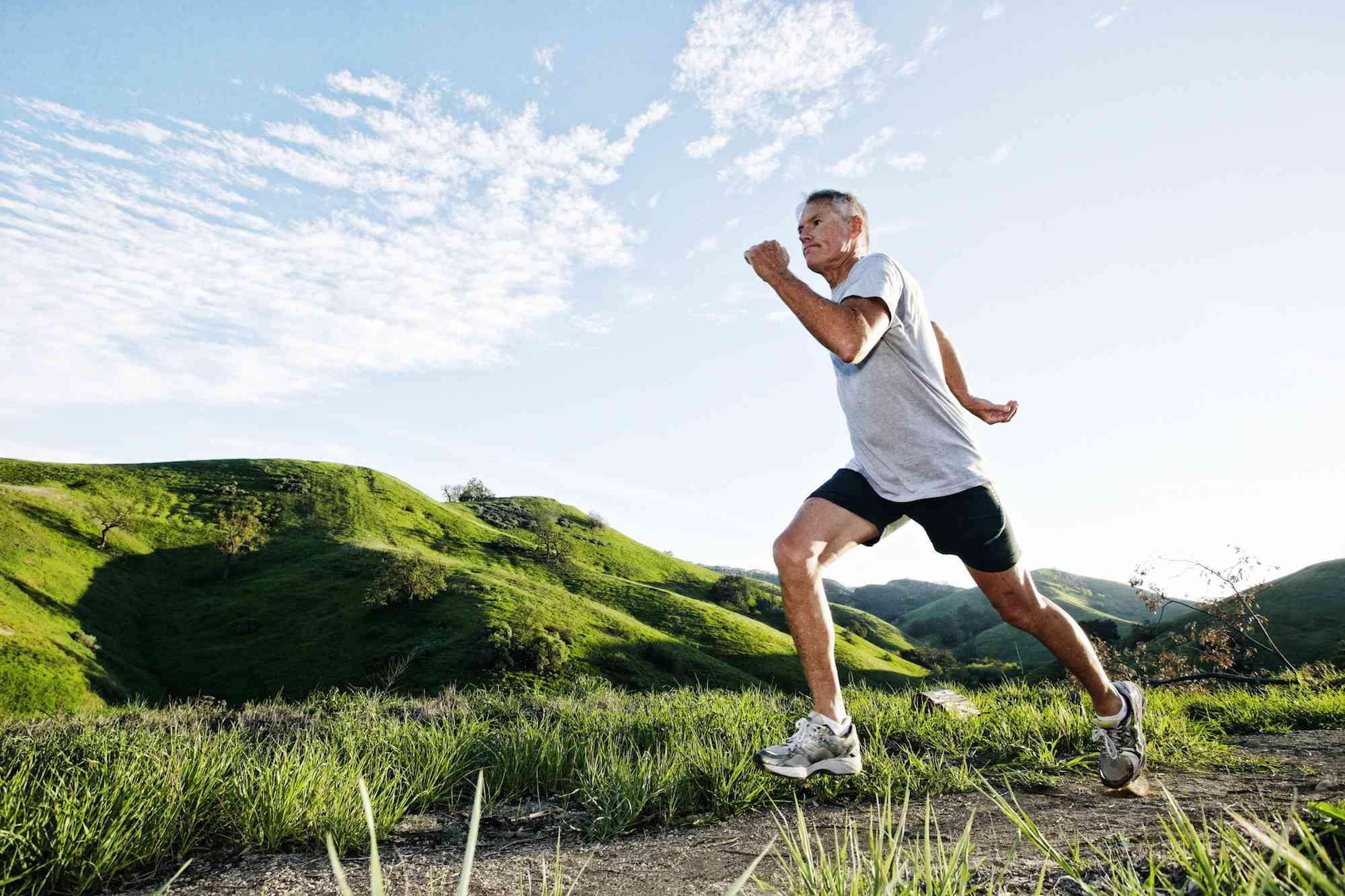 Older man jogging on a dirt path during a sunny day