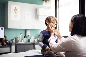 Female doctor examining boy in clinic