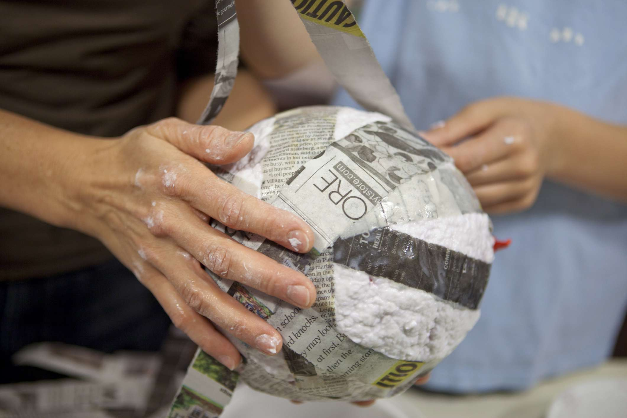 A parent and their child making a paper mache ball