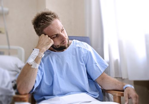 Man patient in hospital room sitting alone