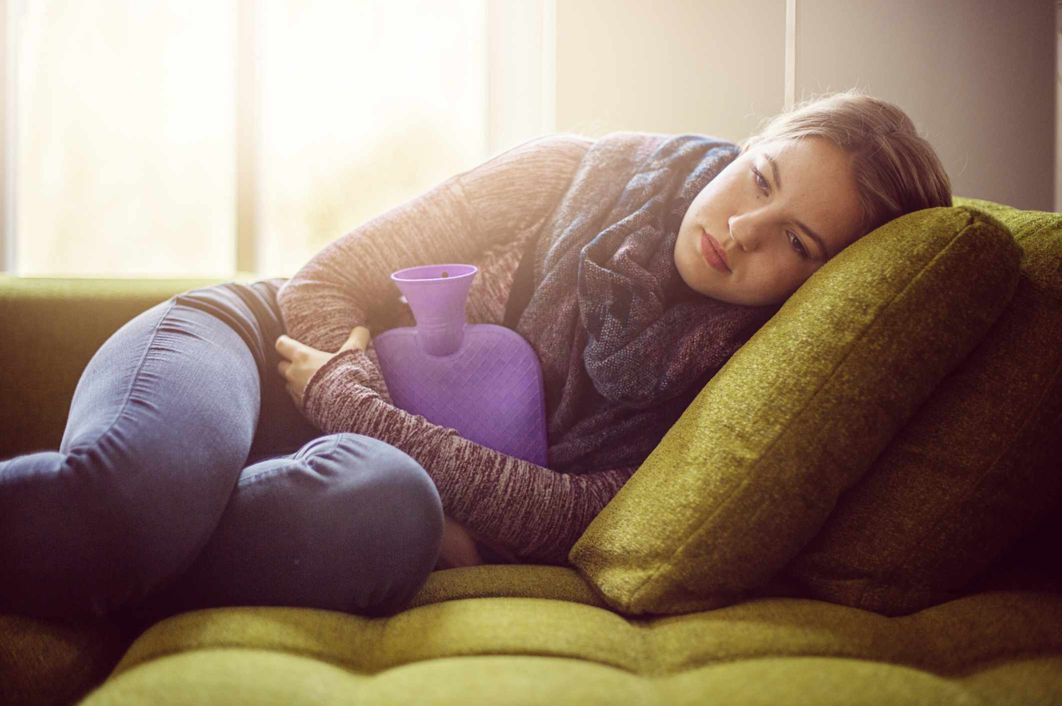 Girl lying on couch with water bottle on stomach