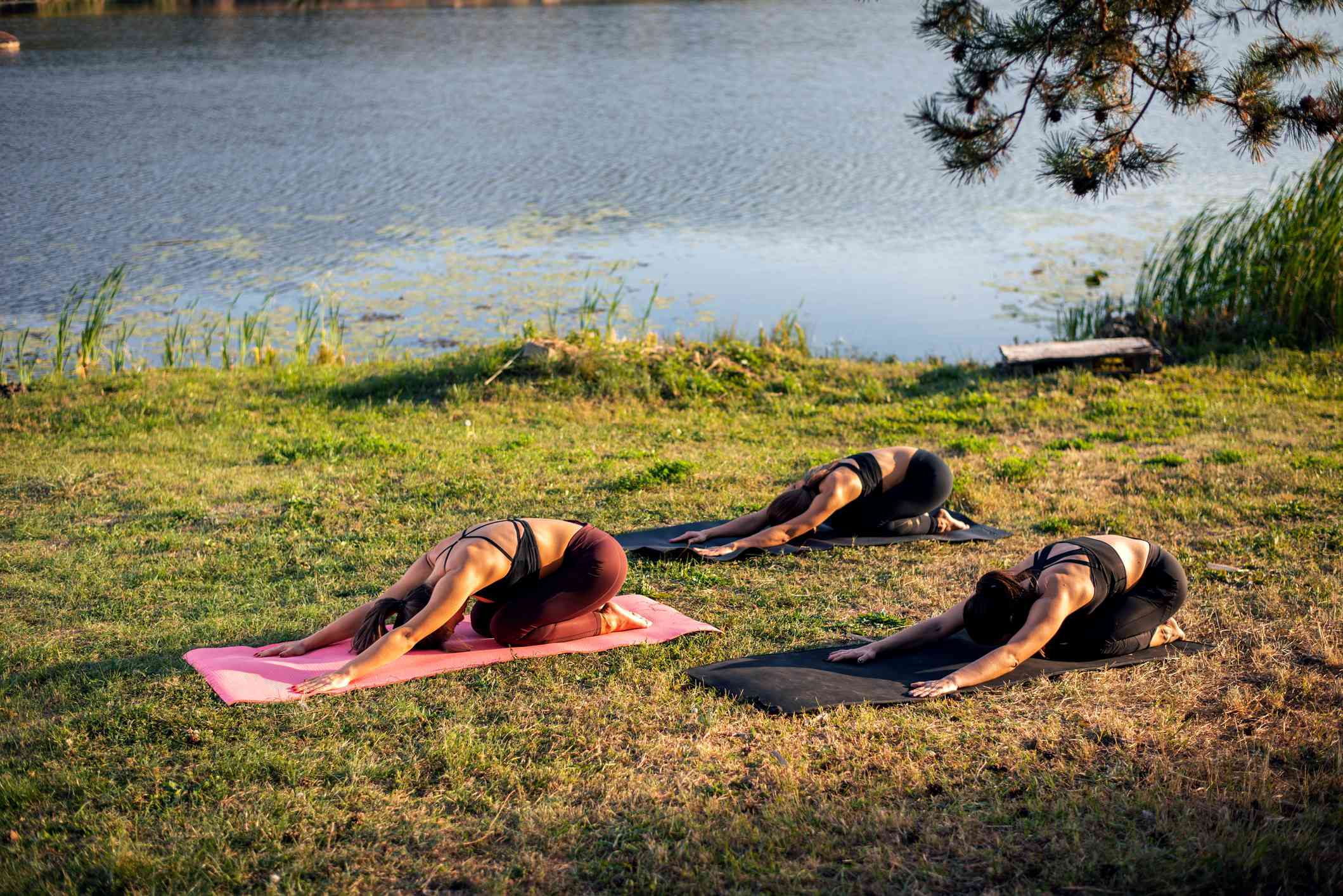Women doing yoga near a lake