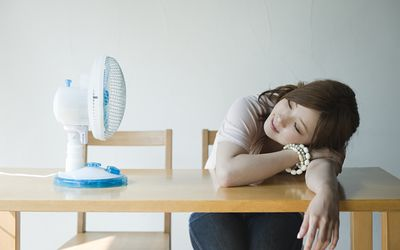 Young woman sitting at desk with fan