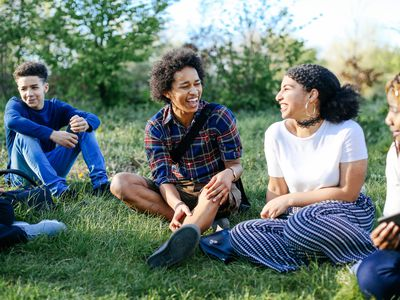 Group of friends sitting on grass, laughing