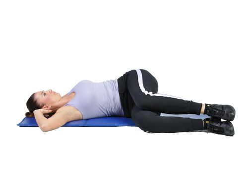a woman in the supine position twists her spine