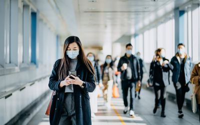 Woman with mask walking through crowd on phone.