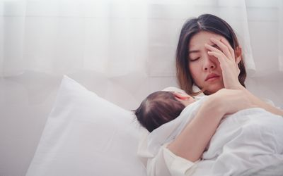 Anxious Woman With Baby Lying On Bed At Home
