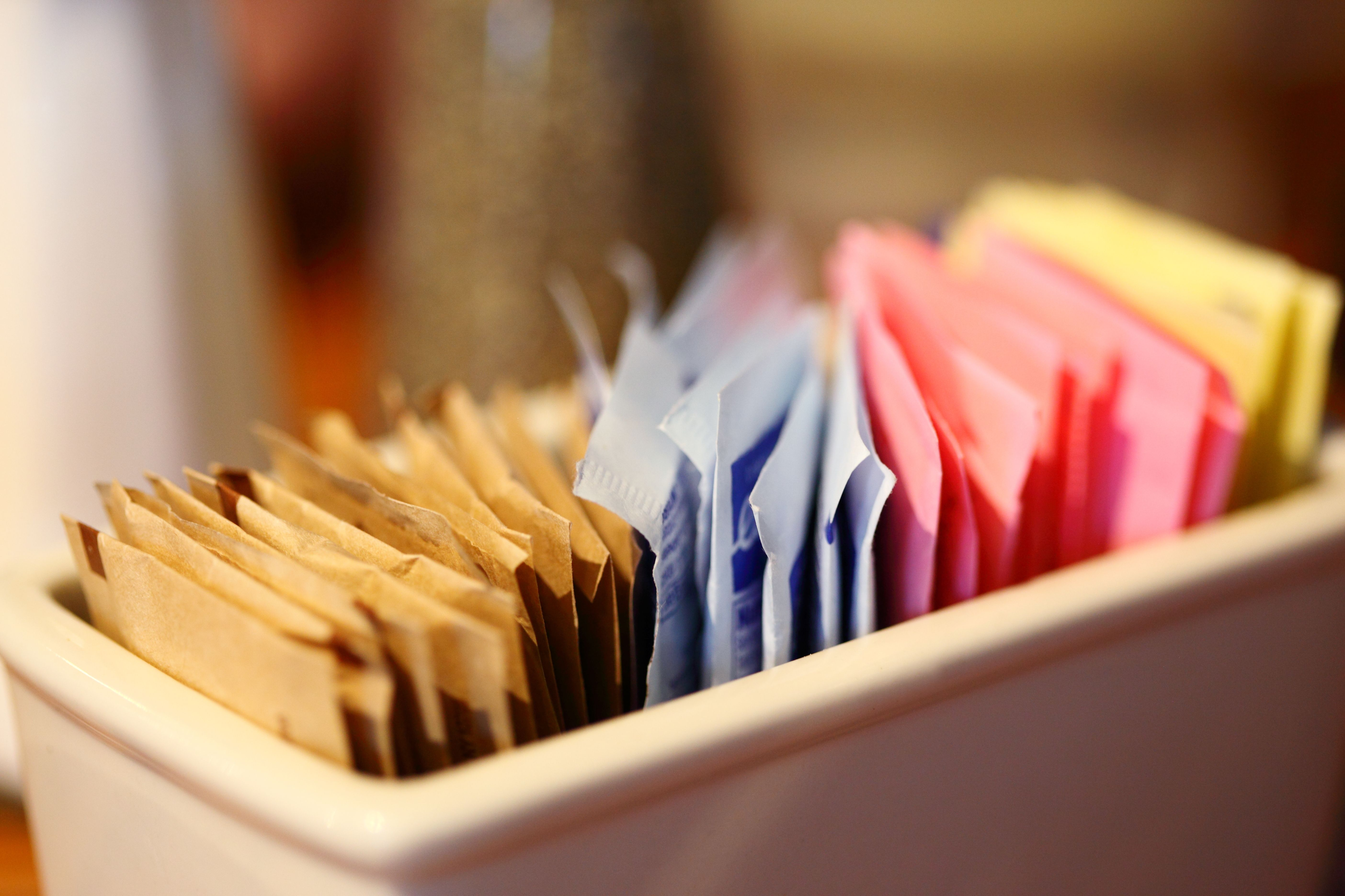 Sugar and sweetener packets in a container