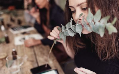 Woman smelling leaves while sitting at table in perfume workshop