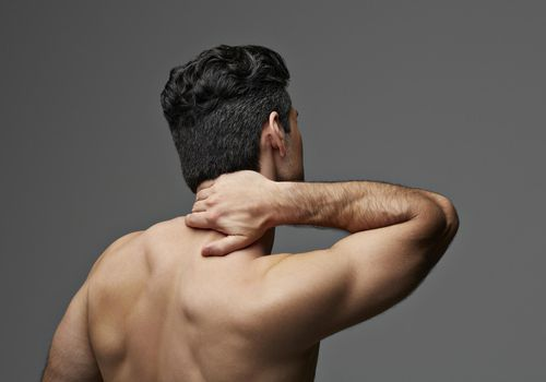Man rubbing his neck.