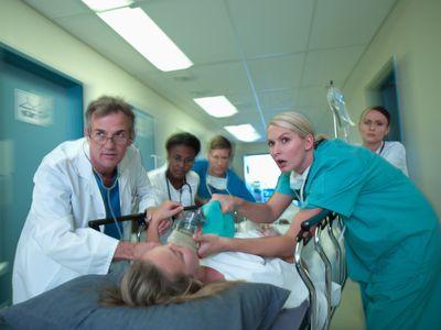 Nurses and doctors wheeling a patient on a gurney