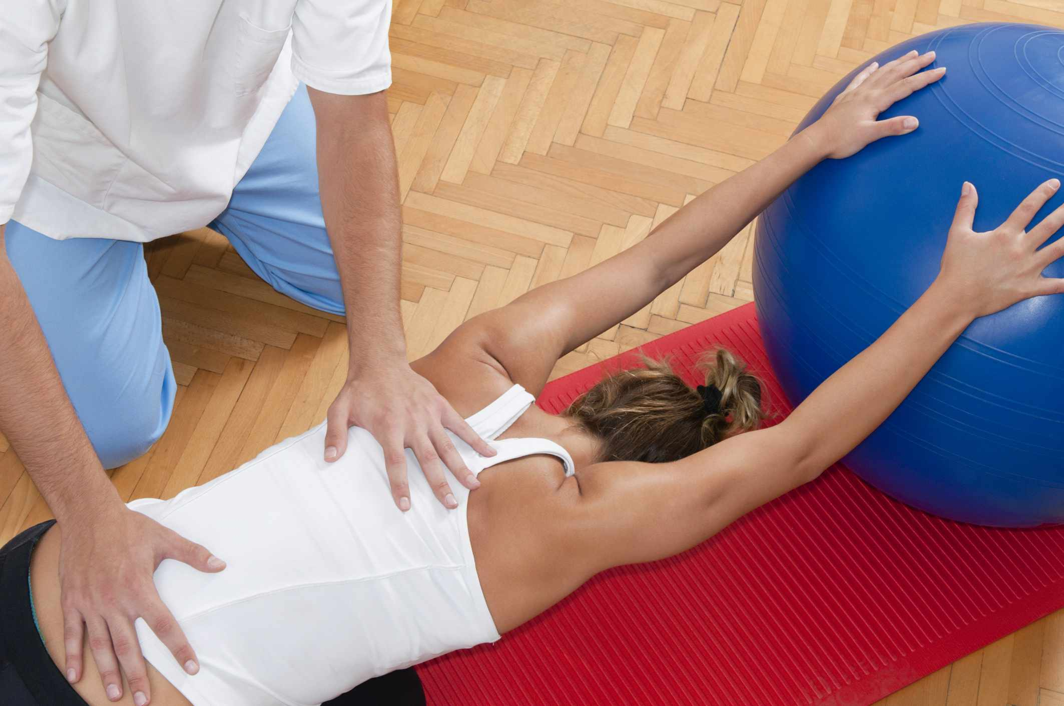 A woman receiving assistance with a back stretch