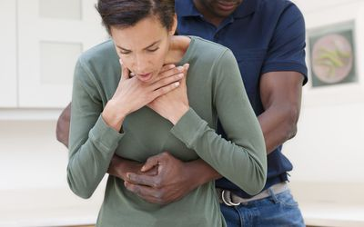 Man performing the Heimlich manoeuvre on a choking woman.