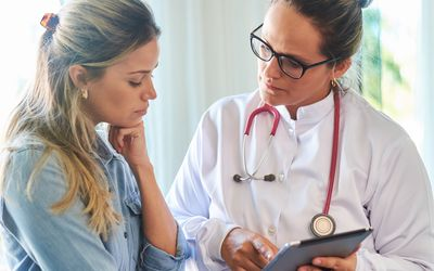 physician talking with female patient about triple positive breast cancer