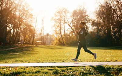 Dedicated African American female athlete running in the park.