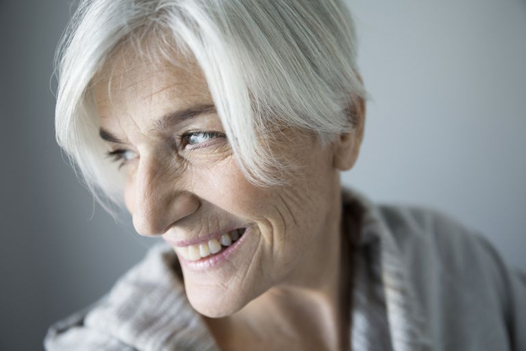 Close up smiling senior woman looking over shoulder