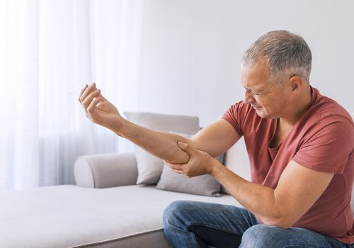 man holding elbow in pain