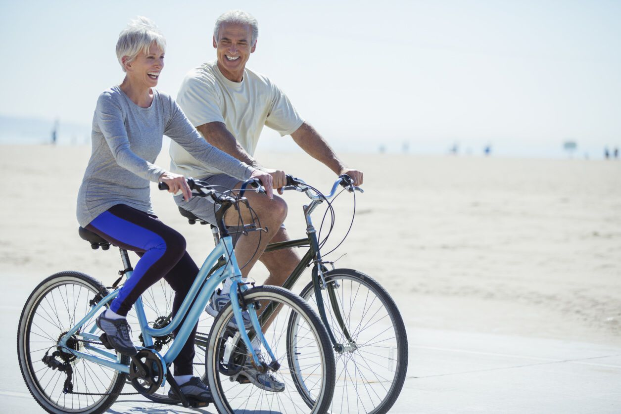 Older couple riding bicycles on the beach