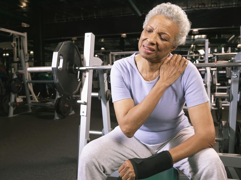 Senior woman in gym rubbing shoulder.