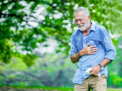 A man alone in the park having chest pain