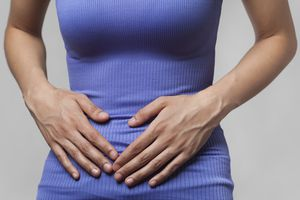 A woman suffering from abdominal pain or cramps.