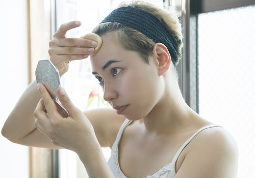 woman applying makeup to face