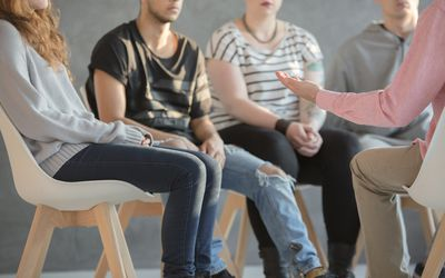 People sitting in a group discussing their eating disorders