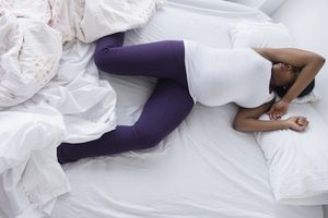 Uncomfortable Black pregnant woman sleeping in bed