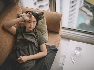 an asian chinese young female lying on sofa with sickness cover with blanket