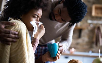 Woman blowing nose while partner brings tea.