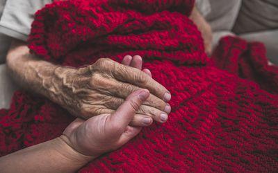 holding elderly hand red blanket