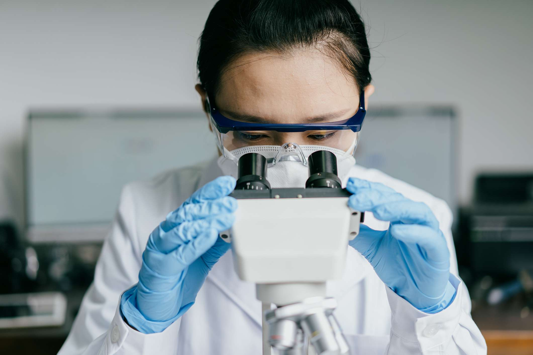 Doctor looking through microscope in laboratory