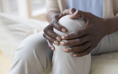 woman holding knee due to knee pain