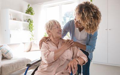 Cheerful nurse taking care of eldery lady