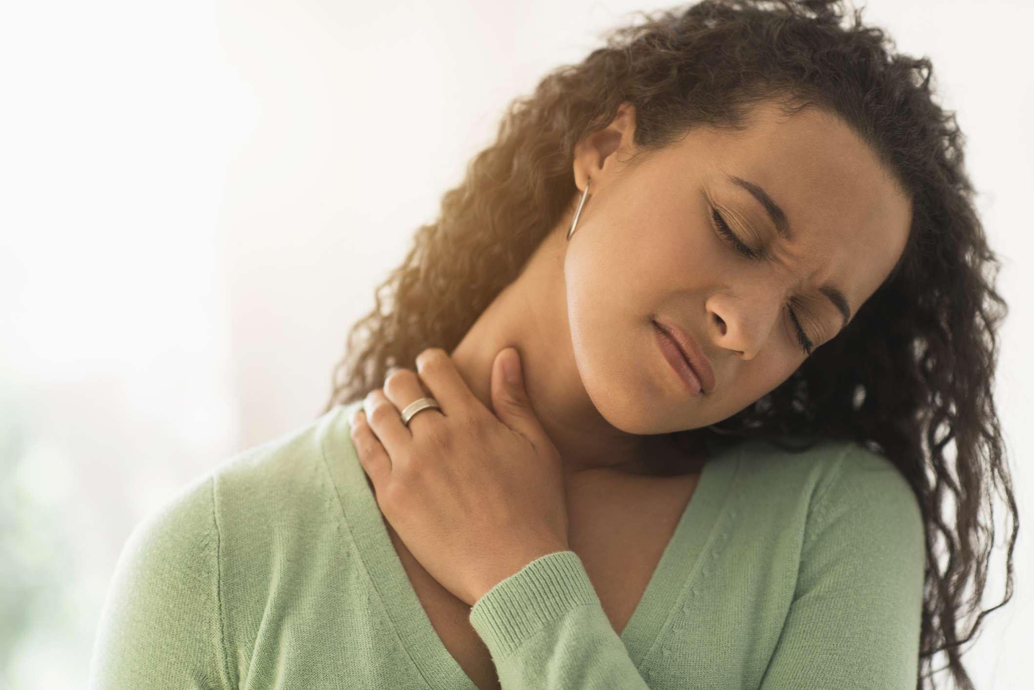 Closeup of mixed race woman rubbing sore neck