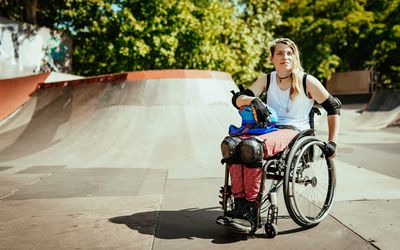 Disabled woman in wheelchair doing stunts in skate park