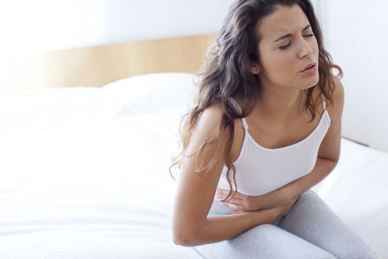 Woman on bed with bad cramps