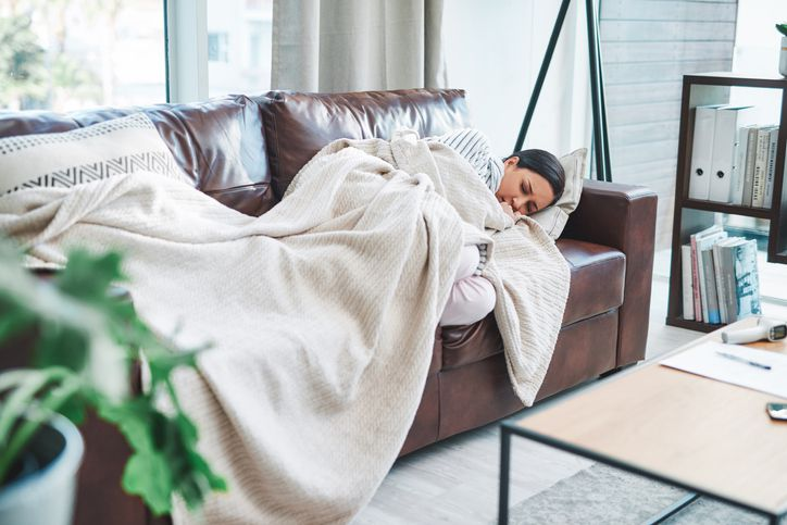 Young woman feeling sick on the sofa at home