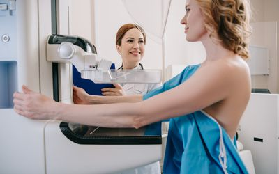 smiling radiologist standing near patient while making mammography diagnostics on x-ray machine