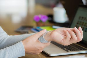 Closeup woman holding her wrist pain from using computer long time.