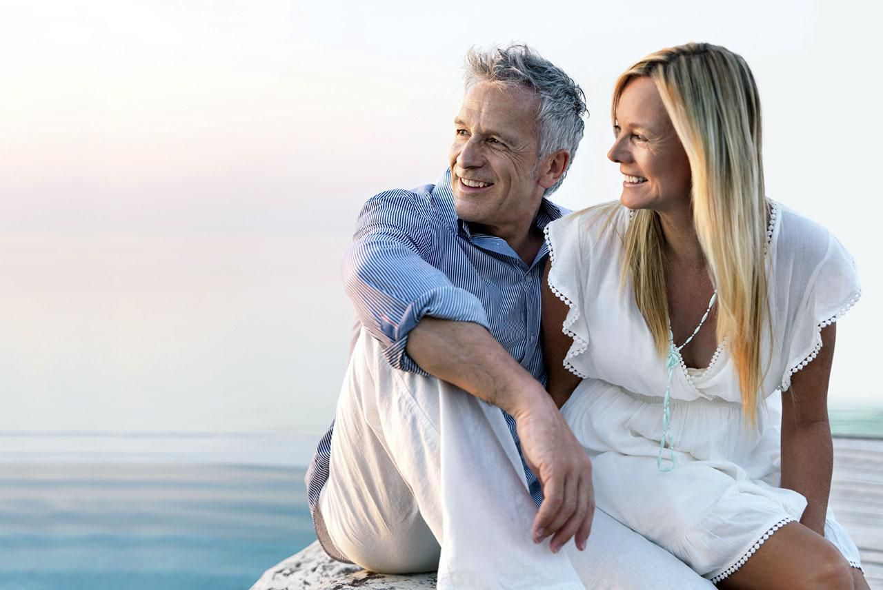 Older man and woman sitting on a rock.