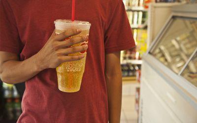 young man drinking a big soda