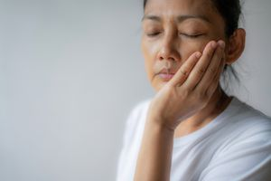 woman suffering from toothache, tooth decay or sensitivity, holding face- stock photo