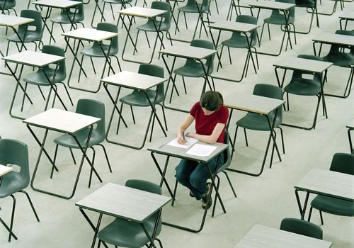 Person taking a test in a room full of desks