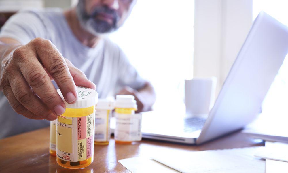 Man looking at prescription medications.