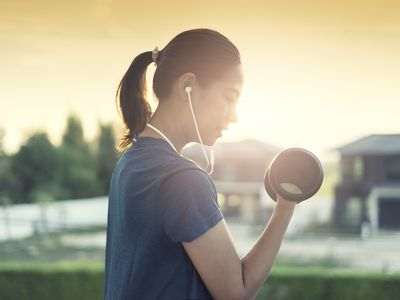 Asian woman work out weight training and listen music
