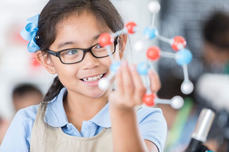 Girl wearing glasses looks at a molecular structure.