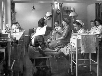 An old hospital where a nurse is bandaging a woman's leg